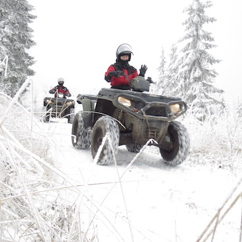 Two friends driving snowmobiles through the snow.