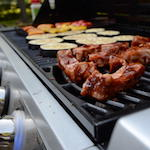 Food cooking on propane-powered grill.