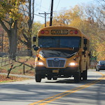 Propane auto-gas school bus driving down residential street.