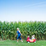 Mother pulling kids in a red wagon with tall, corn stalks and a blue sky in the background.