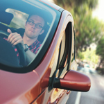 Guy wearing glasses driving a red car