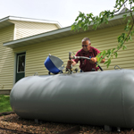 Man filling a propane tank behind a house