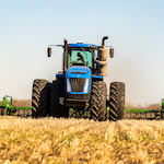 Tractor pulling farm equipment in field