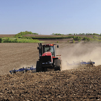 Red ag tractor pulling a tilling in a field