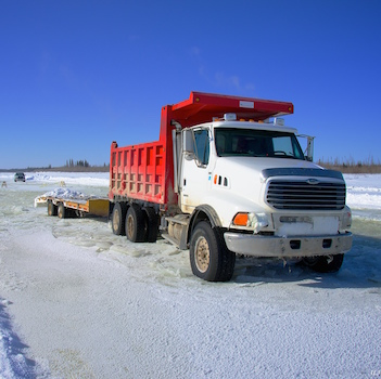 A red and white semi-truck in the winter.