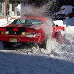 Red muscle car stuck in snow.