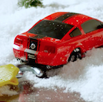 Toy red car being towed out of snow bank.