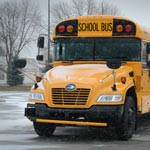 yellow school bus on winter suburban road