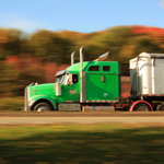 Green semi truck speeding through autumn-leaved scenery