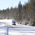 semi truck driving on a snowy road lined with evergreen trees